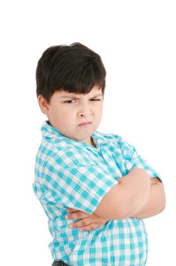 serious little boy with hands folded standing isolated on white